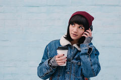 Young hipster girl talking on the phone and drinking coffee. Young hipster girl in a blue denim jacket and hat, talking on the phone and drinking coffee on light Stock Image