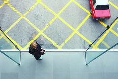 Young hipster girl is using cell telephone. Top view of a woman student with mobile phone in hands is standing on cross street walking bridge with asphalt road Stock Photos