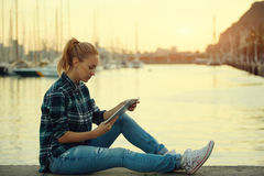 Young hipster girl using touch pad while sitting against sea port background with copy space for your content, Stock Photography
