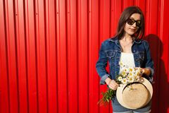Young hipster girl wearing glasses and hat with flowers against red background. Summer outfit. Fashion. Copy Space. Happy hipster girl wearing glasses and hat stock photography