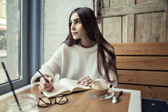 Young hipster girl work in cafe, with note pad in a cafe near window lunch time with coffee. Young hipster girl work in cafe, with note pad in a cafe near window Stock Image