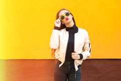Young hipster girl in yellow sunglasses kissing on orange wall. Urban style. Vintage. Glare and light. Young hipster girl in yellow sunglasses kissing on orange Royalty Free Stock Photography