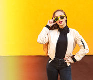 Young hipster girl in yellow sunglasses smiling on orange wall. Urban style. Vintage. Glare and light. Young hipster girl in yellow sunglasses smiling on orange Royalty Free Stock Photography