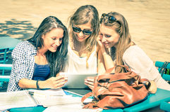 Young hipster girlfriends studying and having fun together. With tablet - Social interaction on new technology trends and internet connection in everyday Stock Photo