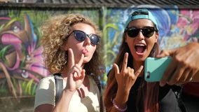 Young Hipster Girls Doing Selfie on Smartphone While Standing Next to the Graffiti Wall. Koh Phangan, Thailand. HD. Two Young Hipster Girls Doing Selfie on stock video footage