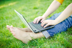 Young hipster girls feet with laptop in a park. Working outdoor Stock Image