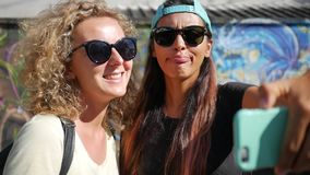 Young Hipster Girls Grimacing Funny Faces and Doing Selfie on Smartphone While Standing Next to the Graffiti Wall. Koh. Two Young Hipster Girls Grimacing Funny stock footage
