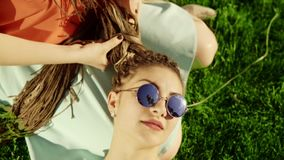 Young hipster girls relaxing on the grass in park. One girl is weaving braids for another. two hipster women laying on. Young hipster girls relaxing on the grass stock footage