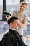 Young hipster guy in barber shop, hairdresser cutting hair with scissors, blow-drying. Concept men place stock photos