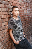 Young hipster guy in a black shirt standing near red brick wall. With graffiti Royalty Free Stock Photography