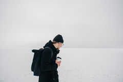 Young hipster guy dressed in black in the winter on the frozen lake with a cup of coffee in hand. And looking into the void Royalty Free Stock Image