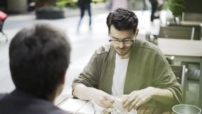 Young hipster guy in glasses in a cafe talking to his friend stock footage