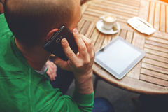 Young hipster guy having having conversation on mobile phone while sitting at the table with touch pad, Stock Image