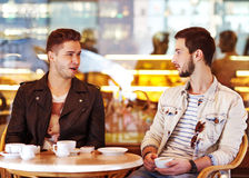 Young hipster guy sitting in a cafe chatting and drinking coffe Stock Photos