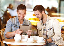 Young hipster guy sitting in a cafe chatting and drinking coffe Royalty Free Stock Photos