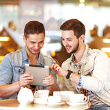 Young hipster guy sitting in a cafe chatting and drinking coffe Stock Images