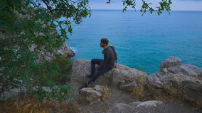 Young hipster guy sitting on the rock mountains near sea, man with a rucksack on his back. Relaxing near ocean stock footage