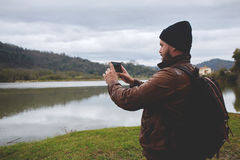 Young hipster guy taking photo on his mobile phone camera of a beautiful landscape while standing near lake Stock Photography