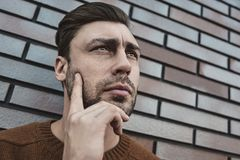 Young hipster guy wearing have some ideas on brick wall background royalty free stock photos