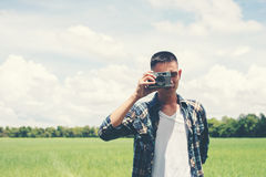 Young hipster handsome man photography standing shooting retro c Royalty Free Stock Photo