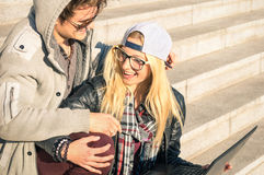 Young hipster happy couple with computer laptop in urban area