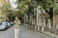 On the Phone. Young hipster with his smart phone in the city street Stock Photography