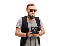 Young hipster holding a polaroid camera. Isolated on white background Stock Images