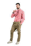 Young hipster holding sunglasses with distrustful look at camera Royalty Free Stock Photo