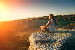 Young hipster with long hair meditates at cliff edge in sunset rays stock images