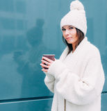 Young hipster looker woman is drinking coffee on the street while walking on cold winter day. Model wearing white coat Stock Photography