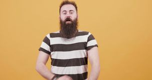 A young hipster looking male show signs of pride and confidence. Man with long black beard crossing his hands in front of his chest and holding them back stock footage