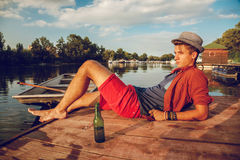 Young Hipster Male. Atracttive Hipster Male Lying Near River Enjoying Sunset Royalty Free Stock Image