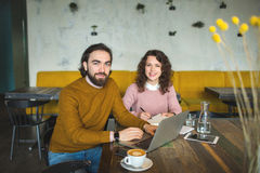 Young hipster male and female working laptop together in cafe. Young hipster male and female working with laptop together in trendy cafe Royalty Free Stock Images
