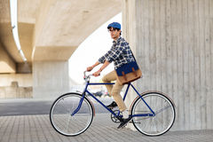 Young hipster man with bag riding fixed gear bike Royalty Free Stock Image