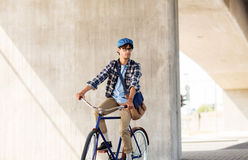 Young hipster man with bag riding fixed gear bike Royalty Free Stock Photos