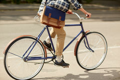 Young hipster man with bag riding fixed gear bike Stock Images