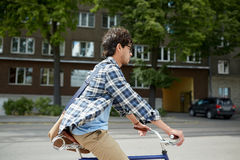 Young hipster man with bag riding fixed gear bike Stock Photo