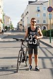 Young hipster man with bicycle walking in the city. Black T-shir. T with print Stock Photography