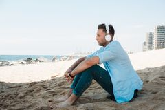 Young hipster man in a blue shirt and jeans listening to music in headphones on a smartphone and is sitting on beach. Sand looking at sea. Digital Music lounge royalty free stock photos