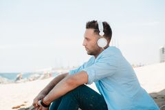 Young hipster man in a blue shirt and jeans listening to music in headphones on a smartphone and is sitting on beach. Sand looking at sea. Digital Music lounge royalty free stock image