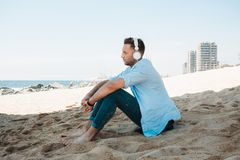 Young hipster man in a blue shirt and jeans listening to music in headphones on a smartphone and is sitting on beach. Sand looking at sea. Digital Music lounge stock images