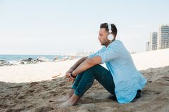 Young hipster man in a blue shirt and jeans listening to music in headphones on a smartphone and is sitting on beach. Sand looking at sea. Digital Music lounge royalty free stock photo