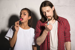 Young hipster man with cigarette near girlfriend eating candy. royalty free stock images