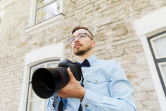 Young hipster man with digital camera in city Royalty Free Stock Images
