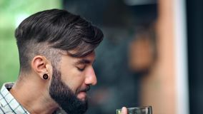 Young hipster man drinking fresh craft beer from glass mug enjoying taste with closed eyes close-up. Handsome bearded guy having thirst drink appetizing dark stock video footage
