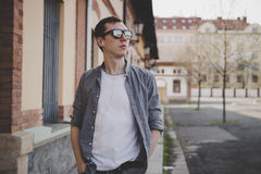 Young hipster man with earphones walking on the street and listening music.  Stock Image