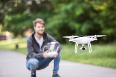 Young hipster man with flying drone. Sunny green nature. Royalty Free Stock Images