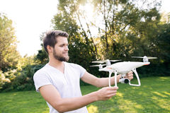Young hipster man holding drone. Sunny green nature. Stock Photos