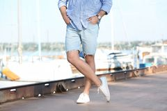 Young hipster man in jean shorts. On pier stock photos