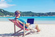 Young hipster man with laptop on tropical beach. Travel, vacation, internet, freelance job concept stock photo